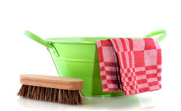 Green metal bucket with cleaning brush